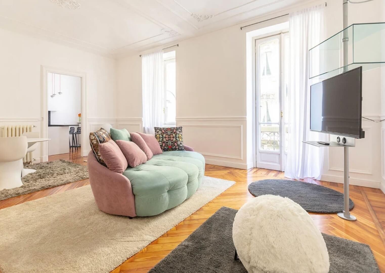 boiserie in soggiorno biannco con divano, televisione e tappeti