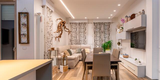 soggiorno ristrutturato a firenze con tavolo, divano e cucina open space